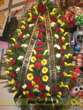 Coroana din cale galbene, frezii albe si galbene si trandafiri rosii